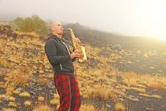 Łysy mężczyzna bawić się na złocistym altowym saksofonie w naturze, przeciw obraz stock