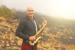 Łysy mężczyzna bawić się na złocistym altowym saksofonie w naturze, przeciw fotografia stock