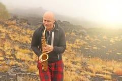 Łysy mężczyzna bawić się na złocistym altowym saksofonie w naturze, przeciw zdjęcia royalty free
