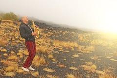 Łysy mężczyzna bawić się na złocistym altowym saksofonie w naturze, przeciw fotografia royalty free
