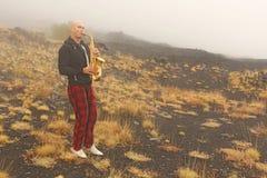Łysy mężczyzna bawić się na złocistym altowym saksofonie w naturze, przeciw obrazy royalty free