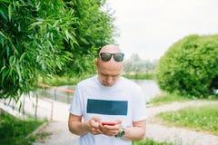 Łysy mężczyzna trzyma telefon w parku z okularami przeciwsłonecznymi zdjęcie stock