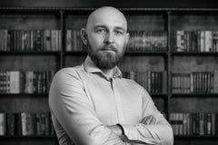 Łysy mężczyzna z brodą w bibliotece obraz royalty free