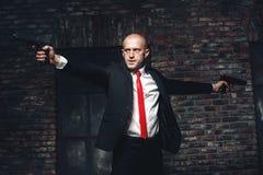 Łysy najęty zabójca w czerwonym krawacie celuje krócicy Fotografia Royalty Free