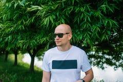 Łysy przystojny mężczyzna w okularach przeciwsłonecznych przy białym tshirt jest przy lato parkiem obraz stock