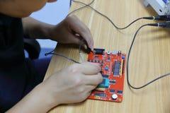 Œmale-Elektronik-Ingenieur ¼ ï Leiterplatte der elektronischen Geräte und, der Oszilloskop im Labor verwendet lizenzfreie stockfotografie