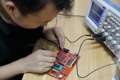 Œmale-Elektronik-Ingenieur ¼ ï Leiterplatte der elektronischen Geräte und, der Oszilloskop im Labor verwendet lizenzfreie stockbilder