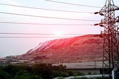 Ściółki sterta blisko elektrycznego pilonu Obraz Royalty Free