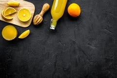 Ściśnięcie sok od pomarańcz Juicer, plasterki pomarańcze, napój w szkle i butelka na czarnego tła odgórnym widoku, kopiujemy Obraz Stock