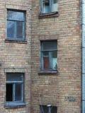 Ściana stary cegła dom z drewnianymi okno, błękit ramami w okno zasłona i niebo, odbija, dobro Zdjęcie Royalty Free