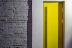 Ściana z cegieł z żółtym drzwi obraz royalty free