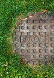 Ściekowy manhole z trawą i słowa niebezpieczeństwem Zdjęcia Royalty Free