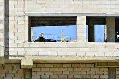 Ścienne nowe domowe białe krzemian cegły z okno który pokazuje pracowników budowlanych w mieście Mogilev, Białoruś Sierpień 2017 Zdjęcie Stock