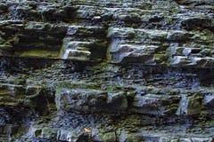 Ścienny kamienny nierówny mokry zakrywający mech ściany siklawy zmrok - szarość nawierzchniowa w górę tło kamienia projekta bazy  fotografia stock