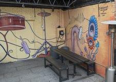 Ścienny malowidło ścienne otacza plenerowego karmowego patio, Głęboki Ellum, Dallas, Teksas Zdjęcia Royalty Free
