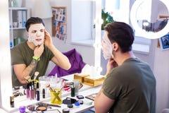 Ścisły mężczyzna koryguje jego gładzi twarzy maskę podczas gdy dostawać gotowy fotografia stock