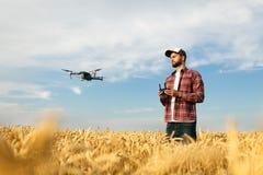 Ścisły truteń unosi się przed rolnikiem z dalekim kontrolerem w jego rękach Quadcopter lata blisko pilota agronom Zdjęcia Royalty Free