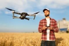 Ścisły truteń unosi się przed rolnikiem z dalekim kontrolerem w jego rękach Quadcopter lata blisko pilota agronom Fotografia Royalty Free