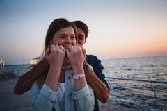 Ściskać pary przy plażą przy wschodu słońca nieba lata czasem, seashore lata plaża przy żółtym błękitnym wieczór horyzontu morzem Obraz Royalty Free