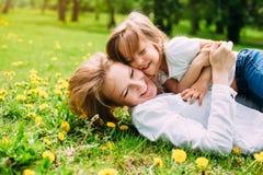 Ściskać szczęśliwej matki i córki dla spaceru w parku Na zielonym gazonie obraz stock