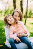 Ściskać szczęśliwej matki i córki dla spaceru w parku Na zielonym gazonie zdjęcia stock