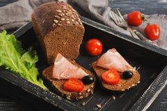 Ściska z baleronem, czarnym chlebem, pomidorami, sałatą i oliwkami na czarnej drewnianej tacy, Obraz Royalty Free