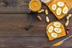 Ściska z dokrętka bananem dla i masłem śniadaniowej grzanki, noża i szklanego słoju z dokrętki pastą, dokrętki na ciemny drewnian Obrazy Royalty Free