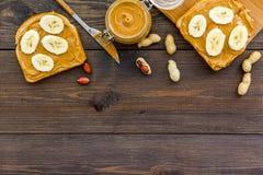 Ściska z dokrętka bananem dla i masłem śniadaniowej grzanki, noża i szklanego słoju z dokrętki pastą, dokrętki na ciemny drewnian Fotografia Stock