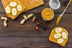 Ściska z dokrętka bananem dla i masłem śniadaniowej grzanki, noża i szklanego słoju z dokrętki pastą, dokrętki na ciemny drewnian Obrazy Stock