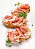 Ściska z piec na grillu kraju chlebem z dodatkiem uwędzonego baleronu i kaparów Zdjęcia Royalty Free