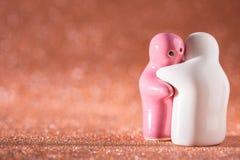 Ściskający Białą i Różową Ceramiczną lalę na abstrakcie Zamazany Defocuse Obrazy Stock