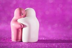 Ściskający Białą i Różową Ceramiczną lalę na abstrakcie Zamazany Defocuse Zdjęcie Royalty Free