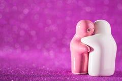 Ściskający Białą i Różową Ceramiczną lalę na abstrakcie Zamazany Defocuse Zdjęcie Stock