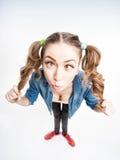 Śliczna śmieszna dziewczyna z dwa koników ogonami krzyżuje patrzeć - szeroki kąta strzał Fotografia Stock
