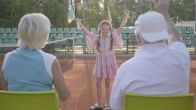 Śliczna śmieszna dziewczyna z dwa pigtails wygrywał tenisowego turniej Jej dziadkowie siedzi blisko z ich plecy kamera zbiory