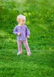 Śliczna śmieszna dziewczynka na trawie Fotografia Stock