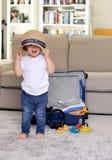 Śliczna śmieszna szczęśliwa mała chłopiec zostaje stawiająca słomianego kapelusz na głowie z błękitną walizką przy tłem w domu pa fotografia royalty free