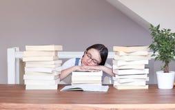 Śliczna śmieszna tween dziewczyna śpi pokojowo z jej głową na książkach między stertą książki w szkłach męczących czytanie i stud fotografia stock