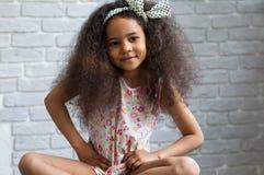 Śliczna afro dziewczyna przeciw szarej ścianie Zdjęcie Stock