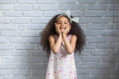 Śliczna afro dziewczyna przeciw szarej ścianie Obrazy Stock