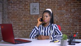 Śliczna afrykańska dziewczyna opowiada nad telefonem i ono uśmiecha się z zrelaksowanym spojrzeniem przy jej miejscem pracy salow zdjęcie wideo