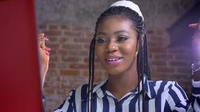 Śliczna afrykańska dziewczyna pokazuje zwycięzcy znaka i śmia się z radością w przodzie jej czerwonego laptop