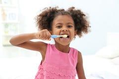 Śliczna amerykanin afrykańskiego pochodzenia dziewczyna szczotkuje zęby w łazience fotografia stock
