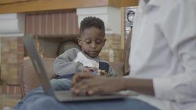 Śliczna amerykanin afrykańskiego pochodzenia kobieta pracuje na laptopie i jej małym ślicznym synu bawić się z zabawkami blisko w zbiory wideo
