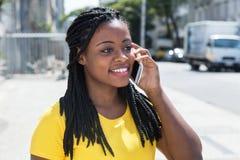 Śliczna amerykanin afrykańskiego pochodzenia kobieta w żółtej koszula przy telefonem komórkowym zdjęcia stock