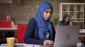 Śliczna arabska kobieta w błękitnym hijab siedzi przy desktop z kolegami za i patrzeje rozochoconą przy kamerą, cegła