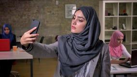 Śliczna arabska kobieta w popielatej hijab pozycji i mienie jej telefon podczas gdy inne dziewczyny w hijabs używają ich komputer