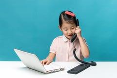 Śliczna Asia mała dziewczynka siedzi przy stołem z jej białym laptopem Zdjęcie Stock