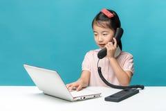 Śliczna Asia mała dziewczynka siedzi przy stołem z jej białym laptopem Fotografia Stock