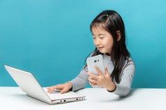 Śliczna Asia mała dziewczynka siedzi przy stołem z jej białym laptopem Obrazy Royalty Free